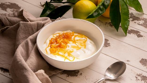 Lemon peel with yogurt and honey on wooden table