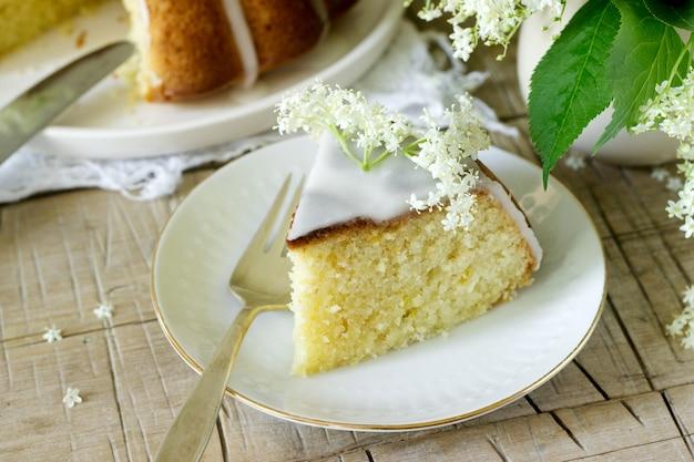 Лимонный пирог с глазурью из сахара и бузины сироп, украшенный цветами бузины. деревенский стиль