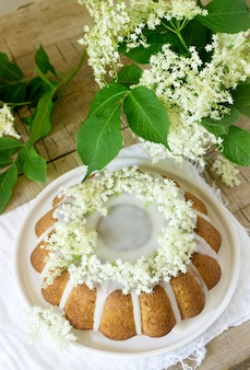 Lemon pie with a glaze of sugar and elderflower syrup, decorated with elderberry flowers. rustic style.