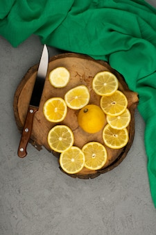 Lemon pieces fresh sour juicy on the brown wooden desk around green tissue on grey