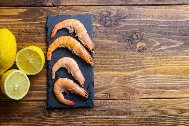 レモン生の新鮮なエビの材料木製テーブルの古典的なレシピ