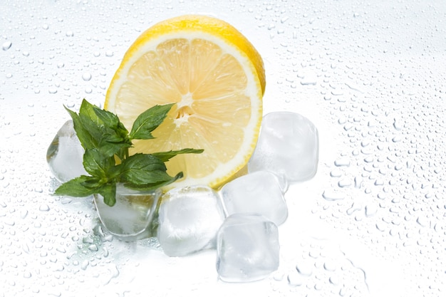 Lemon ring with ice and mint on a silvery background closeup