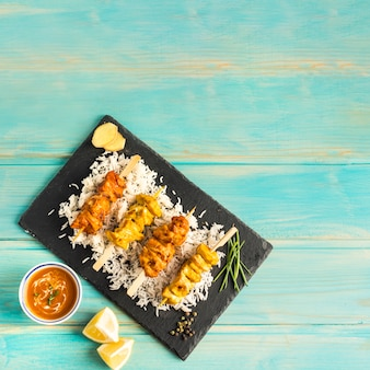 Lemon and sauce near board with chicken kebab
