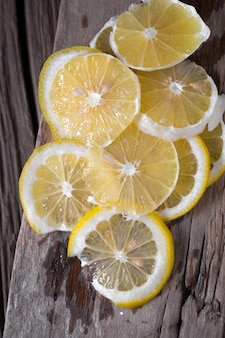 Lemon and side of lemon on dark vintage wood texture background