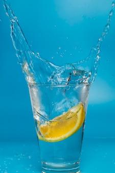 Ломтик лимона падает и падает в разбрызгивающийся стакан