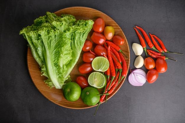 Ломтик лимона, лук-шалот, чеснок, помидоры, салат и перец на деревянной тарелке на черном цементном полу.