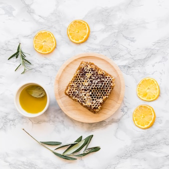 Lemon slice, twig with honeycomb and bowl of oil on white marble background