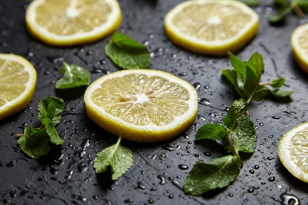 水滴と黒いテーブルの上のレモンスライスと緑のミントの葉。新鮮なトロピカルフルーツ