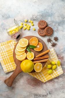 Ломтики лимона, корицы и лайма на деревянной разделочной доске и печенье на белом столе