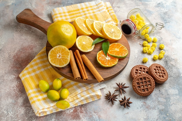 Lemon slices cinnamon lime on a wooden cutting board and biscuits on white table