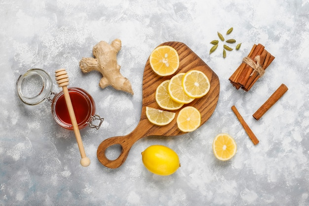 Lemon slices on cutting board,cinnamon sticks,honey on concrete  . top view, copy space
