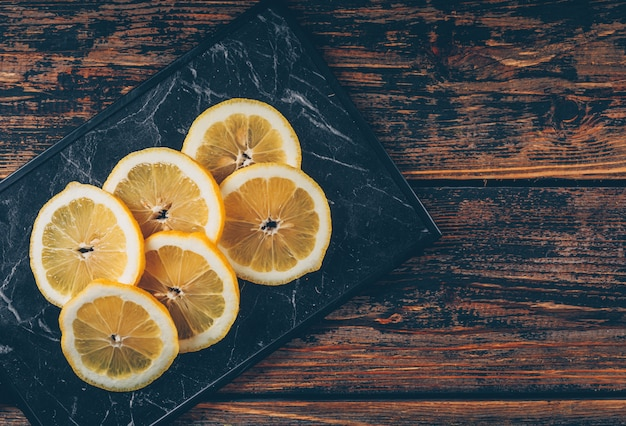 Lemon slices on a cutting board and dark wooden background. flat lay.
