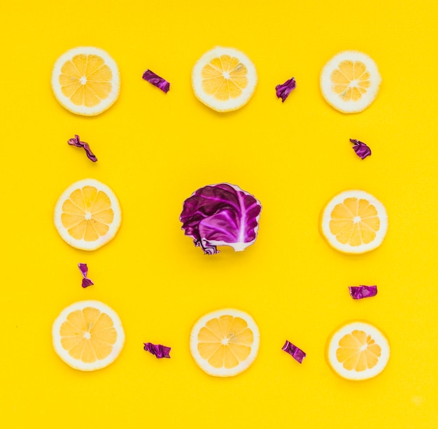 Lemon slices frame with purple cabbage in the center over yellow background
