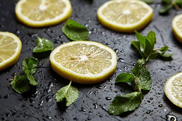 Lemon slices and green mint leaves on black table with water drops. fresh tropical fruit