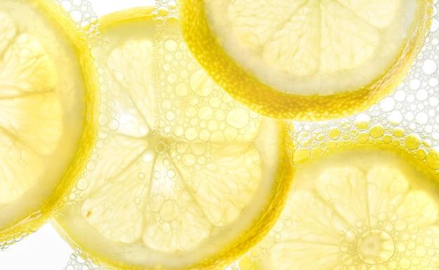 気泡の背景と水中のレモンスライス