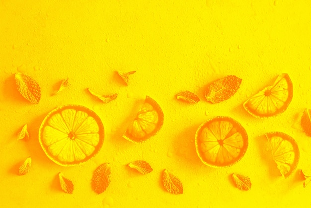 Lemon slices and mint herbs against yellow with copyspace.