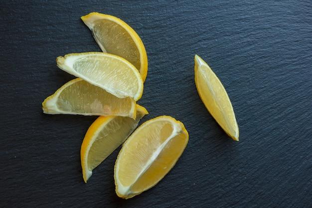 Дольки лимона на темной каменной поверхности. вид сверху. скопировать место для текста