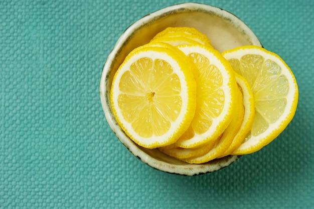 Ломтики лимона над зеленым столом. вид сверху.