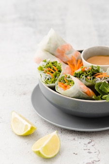 Lemon slices with bowl of shrimp rolls and salad