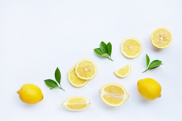 Lemon and slices with leaves isolated on white.