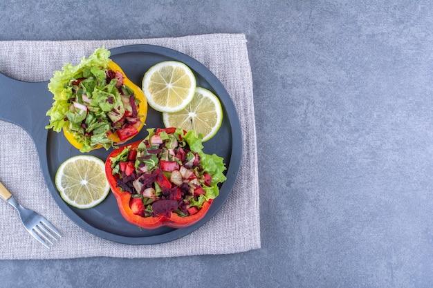 Ломтики лимона с двумя порциями салата в дольках перца на сервировочной сковороде на мраморной поверхности