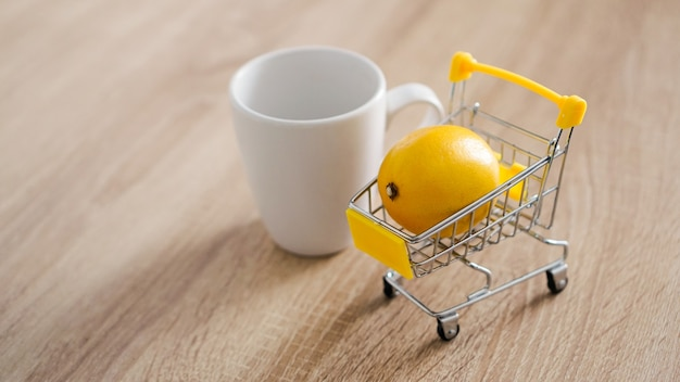 Lemon in a small shopping cart on the kitchen table. nearby is a white mug of tea. light and modern kitchen background.