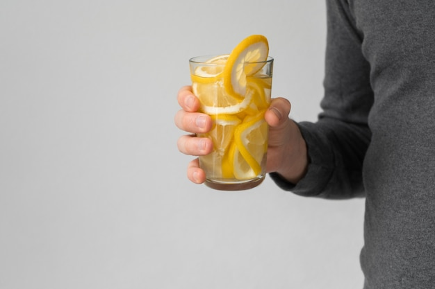 Лимонный коктейль с витамином с. мужская рука держит в руках стакан воды с лимоном. ударная доза витамина с во время пандемии.