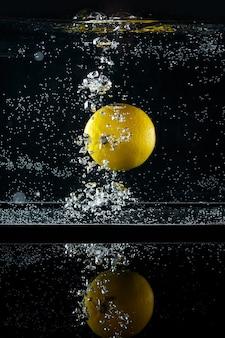 검은 배경에 물에 튀는 레몬