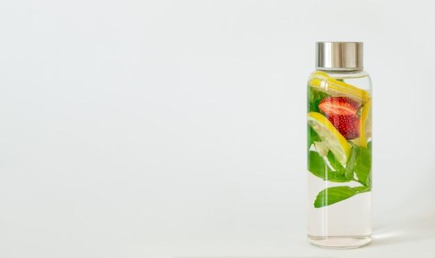 Вода со вкусом лимона, клубники, мяты. летний освежающий напиток. здравоохранение, фитнес, концепция детокс диеты здорового питания. белый фон, копия пространства.