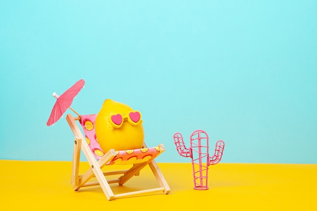 Lemon in sunglasses in the sun bed with umbrella