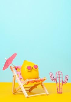 Lemon in sunglasses in the sun bed with umbrella