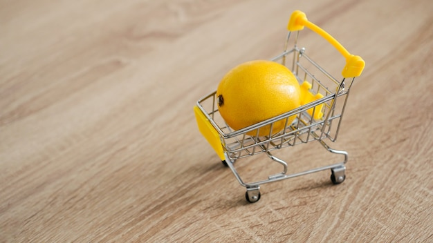 Lemon in a supermarket cart on kitchen table - wooden background. online shopping concept. small budget concept