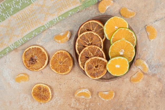 Лимон, мандарин и сушеные апельсиновые дольки на деревянной тарелке.