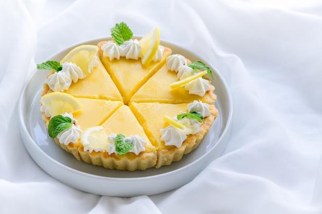 Лимонный пирог цитрусовый в белом блюде и белом фоне ткани, концепция торта и пекарни