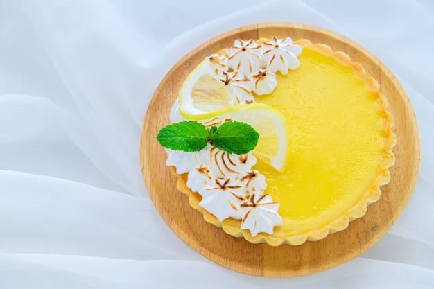 나무 접시와 흰색 천으로 배경, 케이크 및 빵집 개념에 레몬 타트 감귤류 케이크