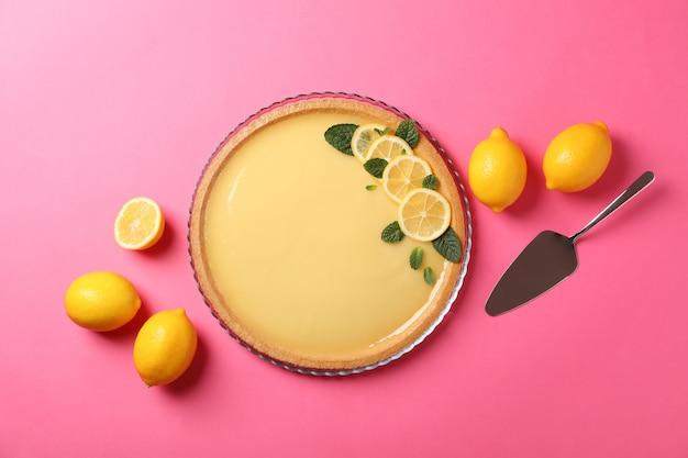 레몬 타르트, 주걱 및 분홍색 배경에 레몬, 평면도