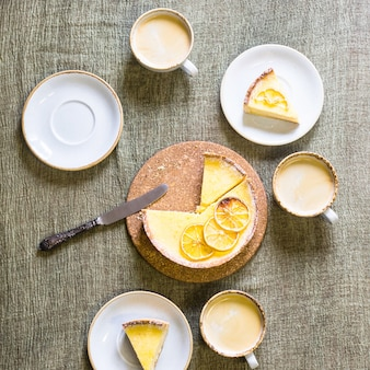 Lemon tart on the table among saucers and cups of coffee.