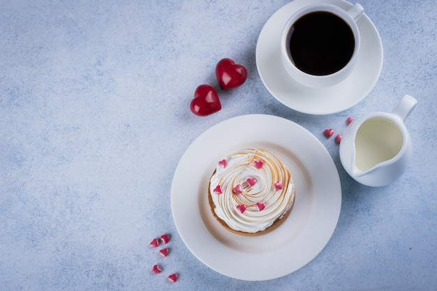 Lemon tart with meringue and cup of coffee, milk with holiday decorations for valentines d