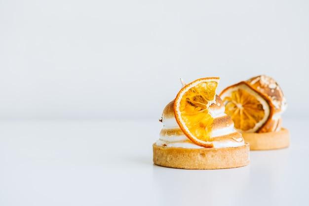 복사 공간이 있는 흰색 배경에 머랭을 넣은 레몬 타틀렛 디저트.