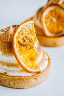 흰색 바탕에 머랭을 곁들인 레몬 타르트 디저트.