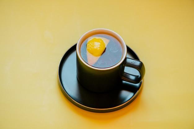 レモンティー。黄色のテーブルにレモンと紅茶。受け皿の黒いカップにレモンとお茶