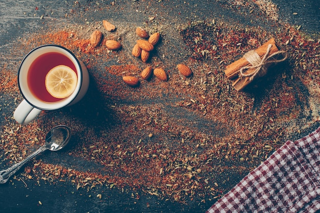 Lemon tea and dried herbs with dry cinnamon, spoon and almond flat lay