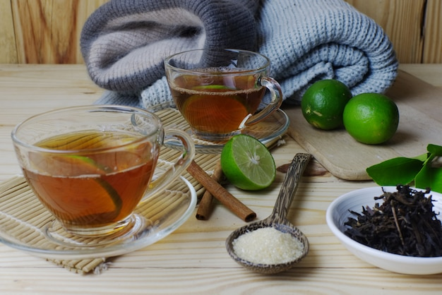 Lemon tea glasses with winter clothes and green lemon with sugar and tea leaves on wooden table.