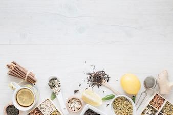 Lemon tea; herbs; strainer and ginger arrange on wooden table