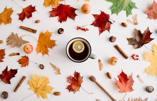 Лимонный чай в рамке из осенних листьев на белом фоне flatlay top view copy space