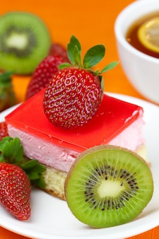 Lemon tea, kiwi,cake and strawberries lying on the orange fabric