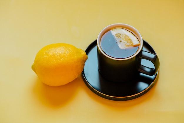 レモンティー。受け皿の黒いカップにレモンのスライスを入れたお茶。