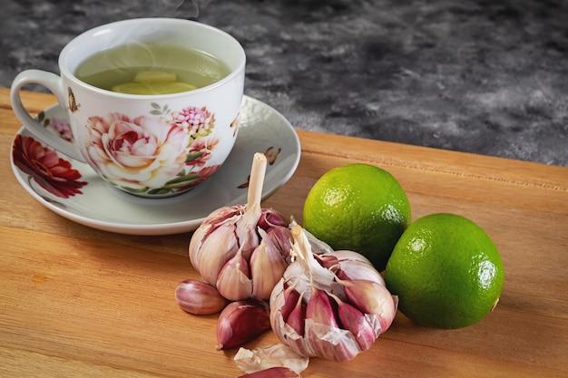 마늘과 레몬 티. 자연 의학에 사용되는 보라색 마늘과 레몬. 레몬 티와 마늘을 곁들인 컵.