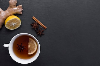 Lemon tea with ginger and cinnamon beside
