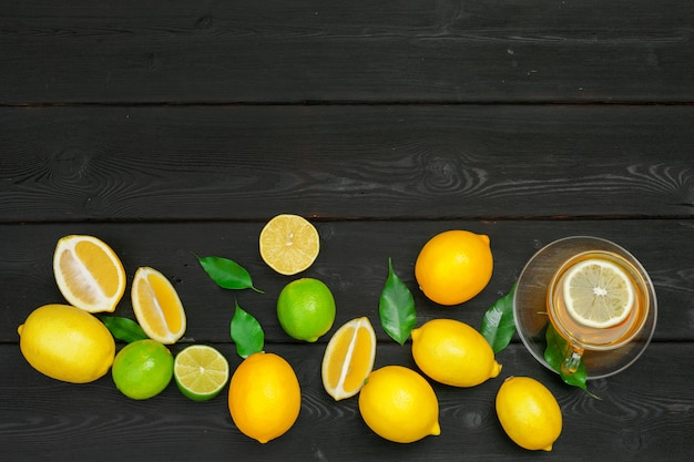 Lemon tea with lemon and lime on wooden table